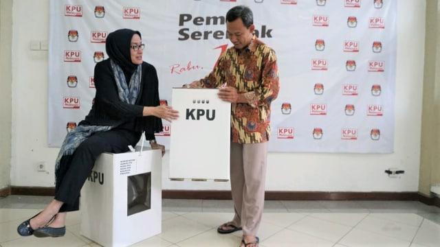 Komisioner KPU RI, Evi Novida Ginting Manik (kiri) dan Pramono Ubaid Tanthowi (kanan), menunjukkan contoh kotak suara di Kantor KPU Pusat, di Jakarta, Jumat (14/12/2018) / Kumparan